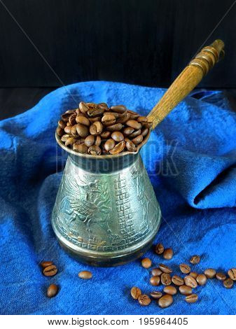 Roasted coffee beans in a cezve on a blue cloth