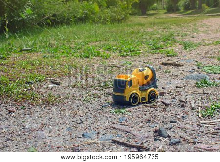 Toy car mixer over the trail near the bushes