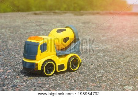 Toy car mixer on the dark asphalt against the backdrop of bushes and trees