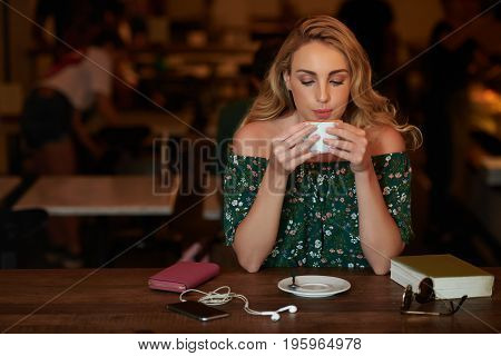 Portrait of attractive blond young woman drinking cappuccino in cafe