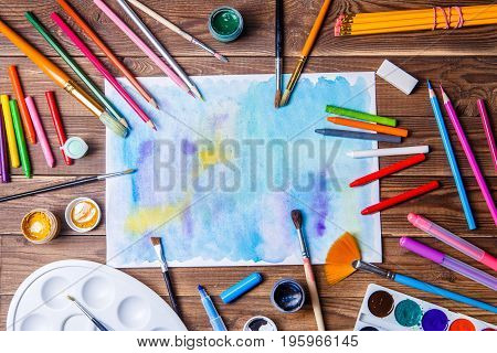Painted paper, brushes, paints, colored pencils and prose stationery. Top view