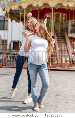 Two pretty women in amusement park having fun and eating sweets, happy family. Samesex lesbian family, pregnant couple