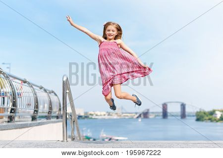 Happy little girl jumping and flying outdoors near the river embankment. Summer vacation and children's games to spend time in the open air.