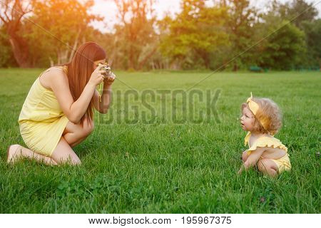 Side view of woman sitting on grass and taking shot of charming baby in costume.