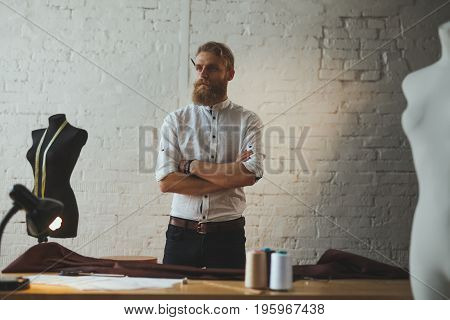 Bearded man wearing white whirt holding arms crossed having pencil behind ear standing in atelier.