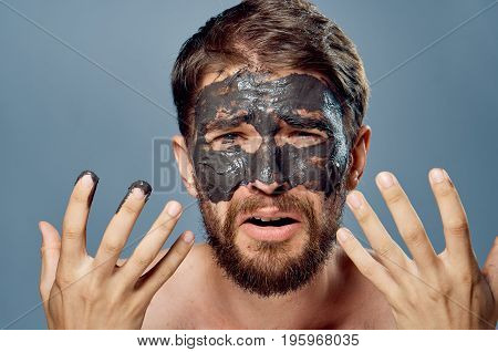 A young guy with a beard on a gray background in a clay facial mask.