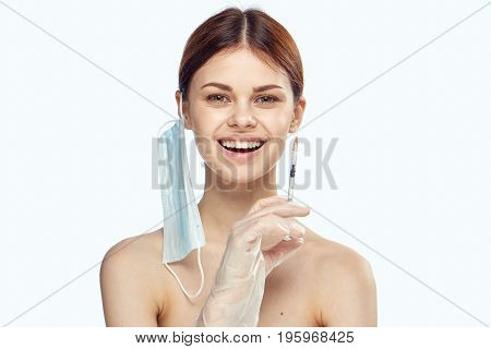 Young beautiful woman on white isolated background holds a syringe, plastic surgery.