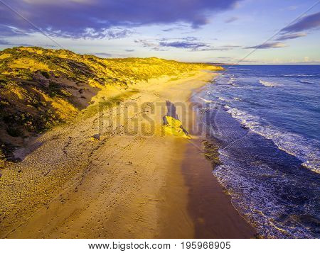 Limestone rock formation with long shadow on ocean beach glowing at sunset