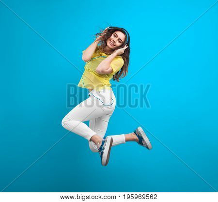 Smiling brunette teenage girl holding headphones jumping against blue background.