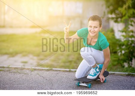 Beautiful girl rides on a highway on Longboard scenic street. Solar toning. Close-up portrait. Healthy lifestyle.