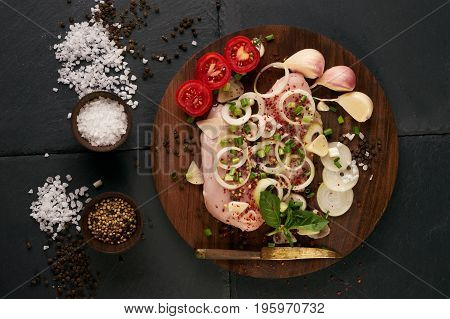 Top view of a chicken fillet for grilled spices tomatoes mushrooms onions on dark stone background. Raw meat chicken for cooking. Delicious balanced food concept. Healthy food low-calories diet.