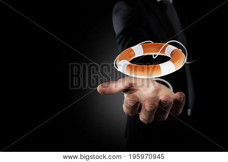 Businessman that hold a small lifebelt. Concept of insurance and help in your business