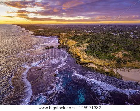 Aerial view of rugged ocean coastline with rural houses in the distance at dusk. Melbourne Australia