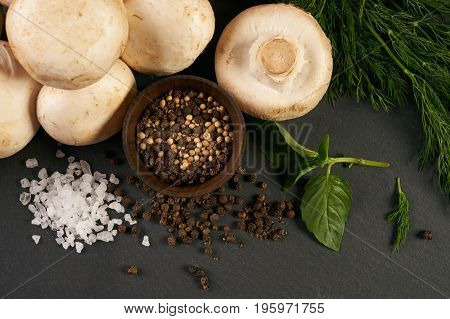 Close-up of a fresh organic ingredients for preparing healthy vegetarian meal mushrooms potatoes onion parsley seasoning spices knife on black stone background top view