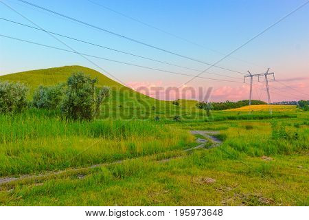 Green grass on a meadow and the height the yellow field with a crop and the blue sky with pink clouds. Russia.