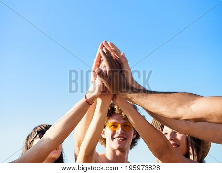 Happy group of friends touching their hands