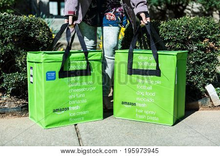 Fairfax USA - March 2 2017: Amazon Fresh insulated grocery delivery bags on front porch closeup with woman picking them up