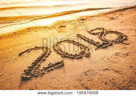 Year 2018 handwritten on seashore sand with sea wave water. Concept of upcoming new year and passing of time.