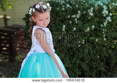 little girl is shy and looks down сute small girl dressed in blue and white dress with a wreath of artificial flowers on her head child in a festive dress on a nature background