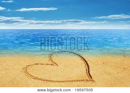 Conceptual heart drown in sand on a beach