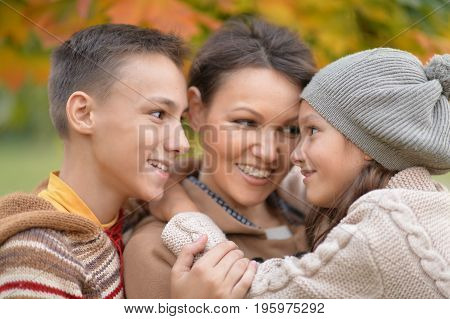 Family portrait of happy mother with children outdoors