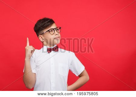 Little boy in bowtie and glasses pointing with finger up on red background having idea.