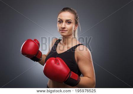 Portrait of woman in red boxing gloves looking at camera and standing in pose.