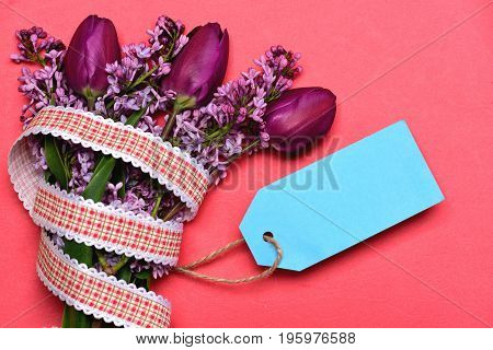 Tulips and lilac flowers in bunch with turquoise note label isolated on light red background top view and copy space. Concept of secret note and womens day