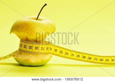 Flexible Ruler In Yellow Color Ties Around Bitten Apple