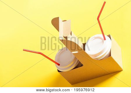 Cardboard bag with paper takeaway cups for hot drinks with white plastic lids and bright red straws isolated on yellow background. Takeout food and beverages concept