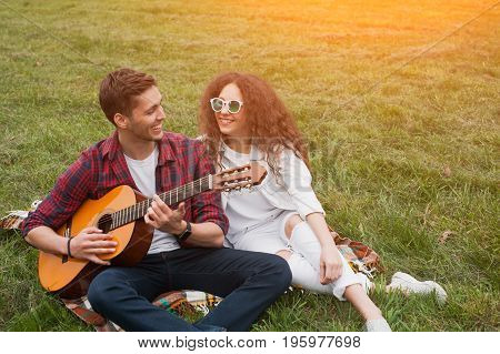 Handsome guy playing guitar sitting on blanket with curvy haired girl smiling.