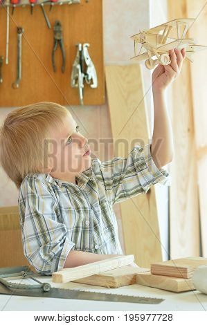 Cute boy sitting at table with model of ship and handsaw and working with wooden planks