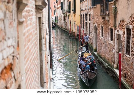Venice, Italy - 21 May 2017 : View Of People On Gondola, With Building Along The Canal In Venice.