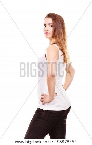 Teenage beauty concept. Portrait of young teenager woman with long brown having neutral face expression wearing white tank top and black leggings