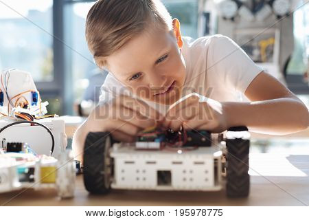 Diligent student. Pleasant fair-haired boy sitting at the robotics class and thoroughly fixing wires in his robotic car, being totally immersed into this process