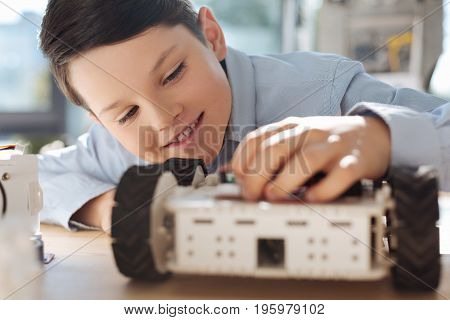 Childlike interest. The close up of a joyful little boy sitting at the table and touching the hood of a robotic vehicle with a great pleasure and interest