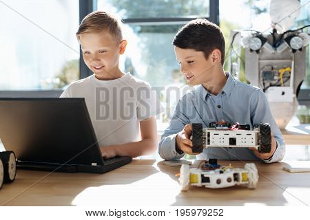 Fruitful collaboration. Pleasant smiling boy sitting at the table, holding a robotic car and observing his peer fair-haired friend programming this robot