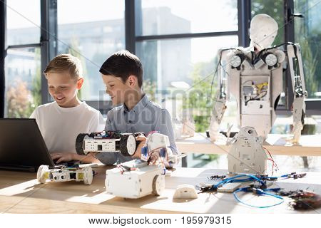 Ambience of creativity. Two charming pre-teen boys sitting in the sun-drenched room with a big human-like robot in it, with one of them holding a robotic vehicle model and the other programming it