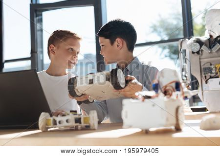 Effective discussion. Pleasant upbeat boys sitting at the table and discussing the details of their common project, one of them holding a vehicle model and the other using a laptop