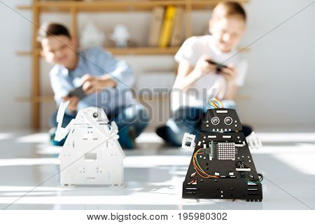 Enjoying themselves. Two cheerful little boys sitting on the floor, holding game controllers and conducting a race between black and white robots being in the focus