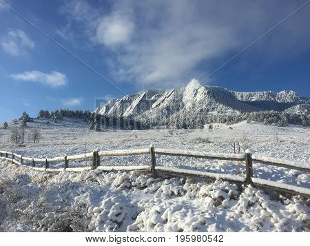 Flatirons in Boulder, Colorado covered in a fresh coating of snow. Cold, snowy winter day