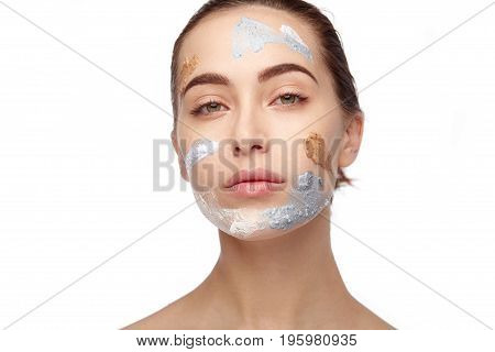 Young model looking at camera with cosmetics on face.