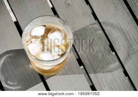 Cold drink with ice cubes on a wooden terrace table