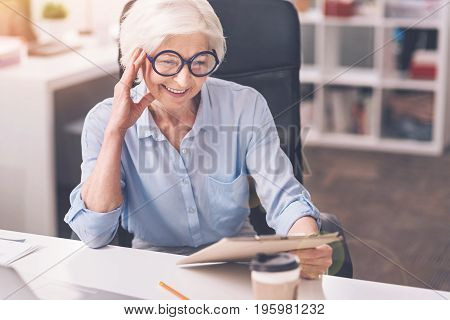 Studying the numbers. Clever successful senior lady having a look at the document using the glasses for this while fulfilling her daily tasks