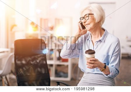 Nice to hear from you. Active accomplished mature lady talking to someone using her smartphone while having a short coffee break at her workplace
