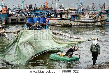 Fisherman bringing baskets with shrimps to the shoreside. December 26 2013 - Da Nang, Vietnam