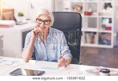 A way for success. Classy competent mature woman working at the office and analyzing a report and sales while thinking about new economic strategy