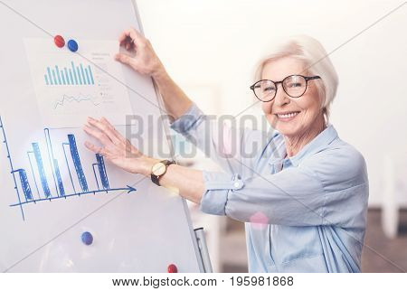 Visualizing the numbers. Inventive experienced classy woman developing better strategy for her company while comparing and analyzing recently obtained data