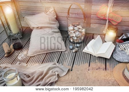 Maritimes still life with candle light and book on a wooden terrace for a time out