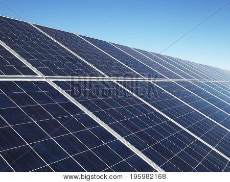 Row of solar panels generating green energy with blue sky